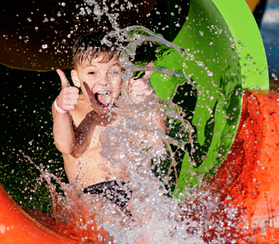 Boy on a waterslide showing thumbs up